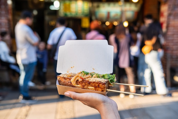 Young woman traveler walking holding stinky tofu at taiwanese street food, travel lifestyle concept