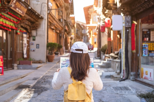 Young woman traveler walking in the old town, shangri-la and looking the map, travel concept