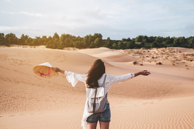 Young woman traveler walking at red sand dunes in vietnam, travel lifestyle concept