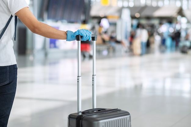 Young woman traveler wearing nitrile glove holding handle luggage in airport terminal, protection coronavirus disease (covid-19) infection. new normal and travel bubble concept