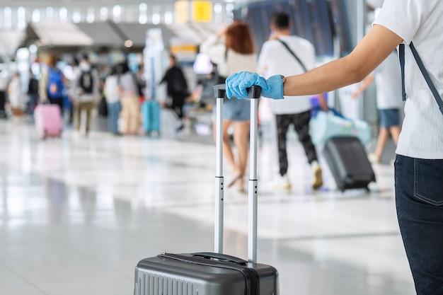 空港ターミナルでハンドル荷物を保持しているニトリル手袋を身に着けている若い女性旅行者