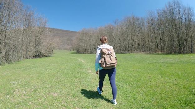 バックパックを背負った若い女性旅行者は、牧草地や森を通り過ぎてトレイルを歩きます。旅行や野外活動のコンセプト。背面図。 4k uhd