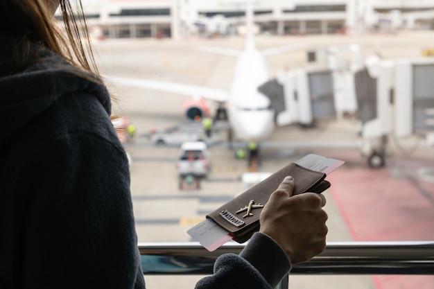 수하물을 들고 비행기를보고 여권을 가진 젊은 여자 여행자