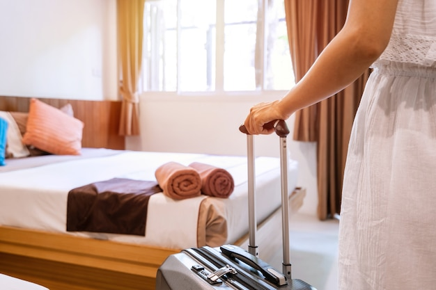 Young  woman traveler with luggage in hotel room on summer vacation