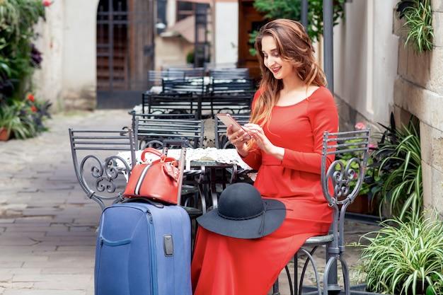 Путешественник молодой женщины с чемоданом использует ее телефон в кафе-ресторане на открытом воздухе.
