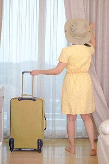 Young woman traveler in yellow dress with her luggage arrives at the hotel room and open curtain for enjoying an outside view, happy women lifestyle with holiday summer travel vacation concept