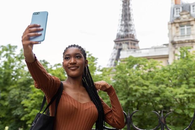 여행을 하고 파리에서 즐거운 시간을 보내는 젊은 여성