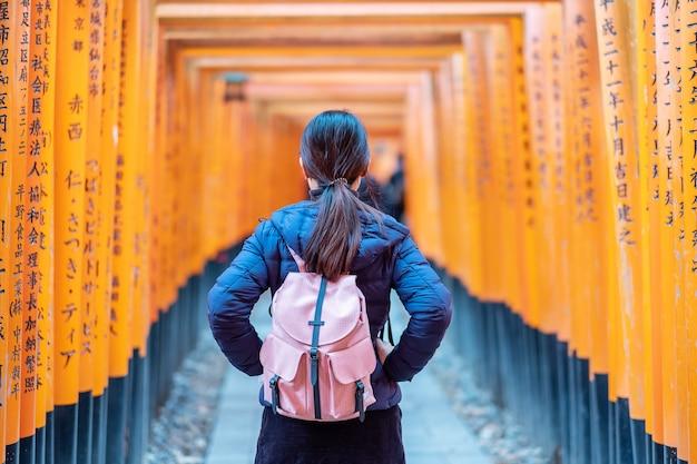 Молодая женщина путешествуя на святыне fushimi inari taisha, счастливый азиатский путешественник смотря яркие оранжевые ворота torii. достопримечательности и популярные для туристов достопримечательности в киото.