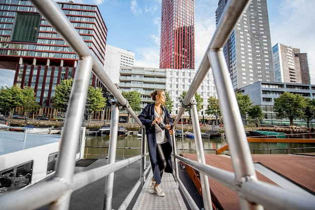 ロッテルダム市の背景に高層ビルと近代的な港を旅する若い女性
