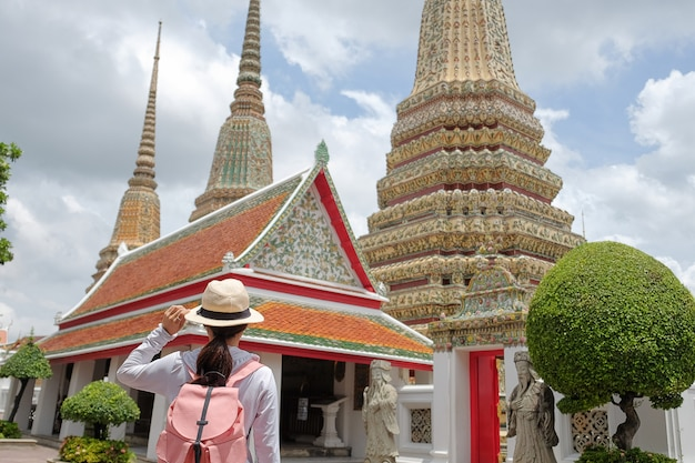 Young woman traveling backpacker with hat, asian traveler looking to pagoda at wat pho