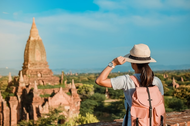 Young woman traveling backpacker with hat, asian traveler standing on pagoda
