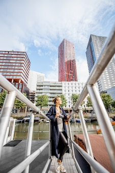 Young woman traveling at the modern harbor with skyscrapers on the background in rotterdam city