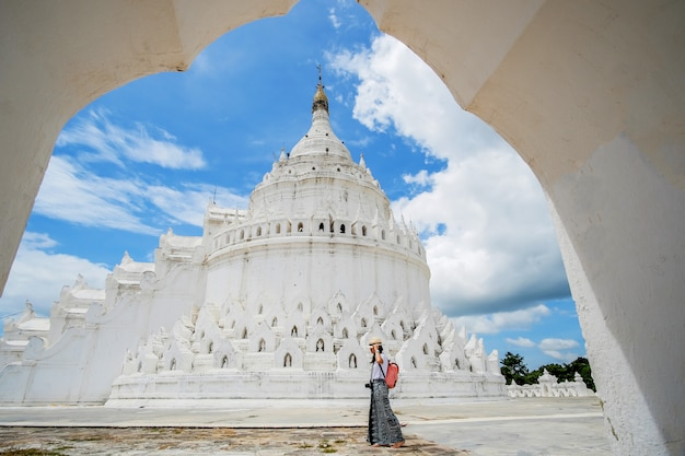 Young woman traveling with bag visit hsinbyume pagoda (mya thein dan) or called white taj mahal of irrawaddy river, located in mingun, sagaing region near mandalay,