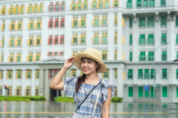 若い女性が帽子と一緒に旅行、幸せなアジアの旅行者がシンガポールのクラークキーでカラフルな虹の建物で訪問します。ランドマークで、観光スポットに人気があります。アジア旅行のコンセプト