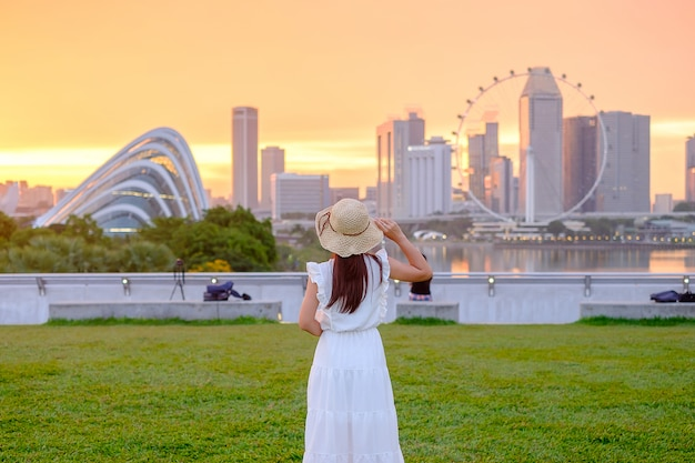 Young woman traveling with hat at sunset, happy asian traveler visit in singapore city downtown. landmark and popular for tourist attractions. asia travel concept