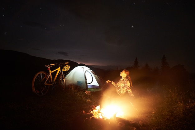 Young woman traveller having a rest at night camping near burning campfire, illuminated tourist tent, mountain bike under beautiful evening sky full of stars