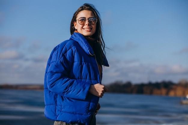 ビーチで青いジャケットの若い女性旅行者