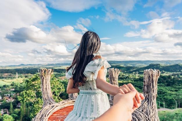 Парень путешественника молодой женщины ведущий к горному виду kho khao пика phukaew на phetchabun, таиланде. путешествуем вместе.