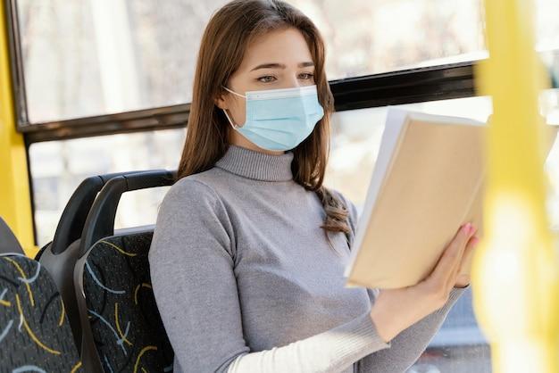 本を読んで市バスで旅行する若い女性