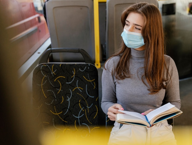 Young woman travelling by city bus reading a book