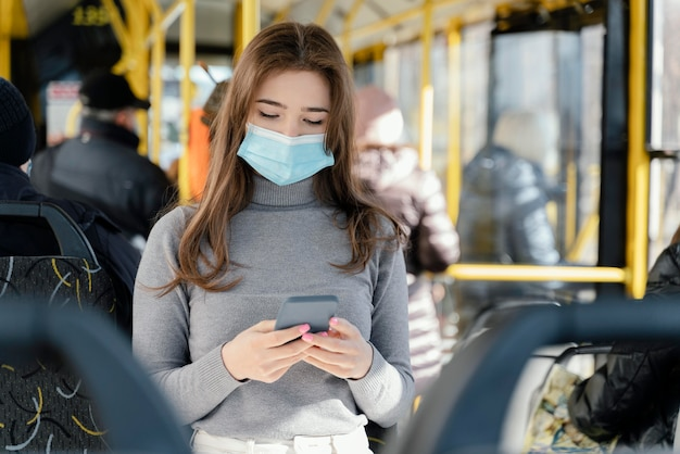 Young woman travelling by city bus using smartphone