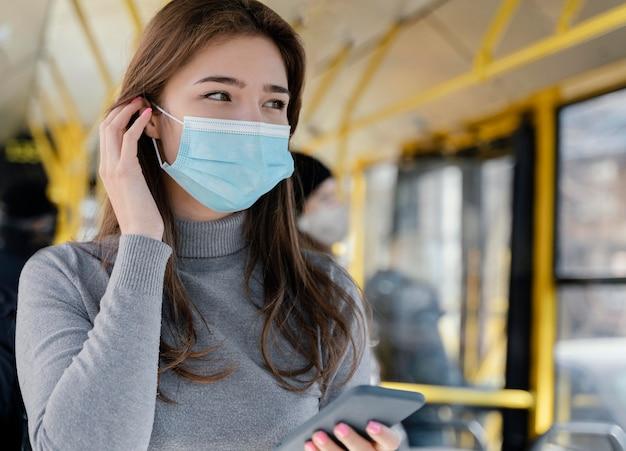 Молодая женщина, путешествующая на городском автобусе с помощью смартфона