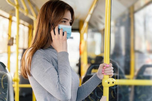 스마트 폰을 사용하여 시내 버스로 여행하는 젊은 여자
