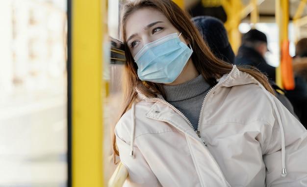 Giovane donna che viaggia in autobus urbano con mascherina chirurgica