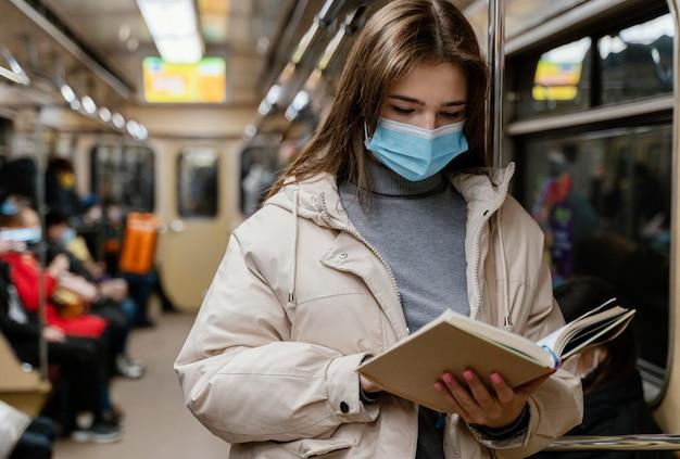 本を読んで地下鉄で旅行する若い女性
