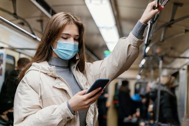 スマートフォンを使用して地下鉄で旅行する若い女性 Premium写真