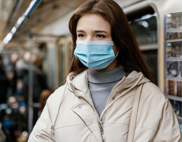 サージカルマスクを着用して地下鉄で旅行する若い女性