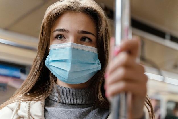 Giovane donna che viaggia in metropolitana che indossa una mascherina chirurgica