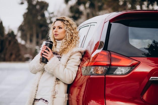 車で旅行し、コーヒーを飲むために雪でいっぱいの道路に立ち寄った若い女性