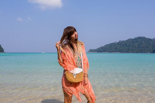 Young woman in trendy boho beach dress