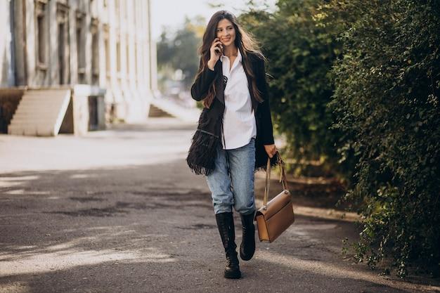 Giovane donna in abito alla moda che cammina nel parco