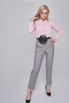 Young woman in trousers and a pink shirt. girl posing on a gray wall. hairstyle. girl with a black handbag on a train. fashion photo