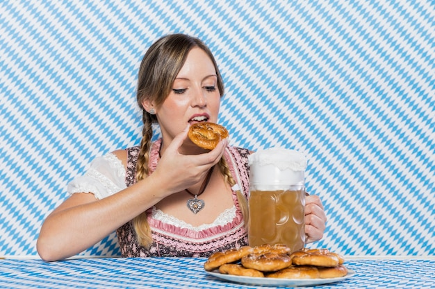 Young woman trying bavarian pretzels