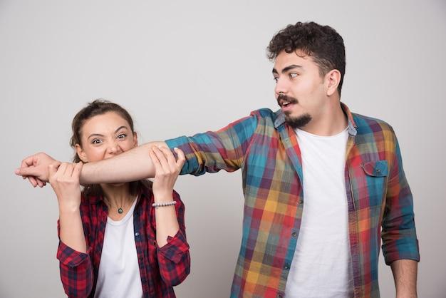 Giovane donna che cerca di mordere la mano dell'uomo su un muro grigio.