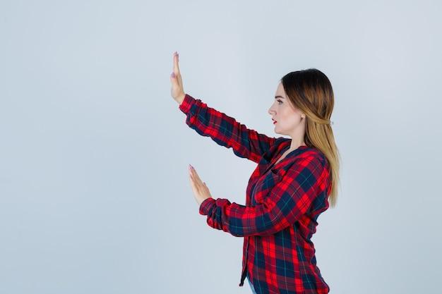 Giovane donna che cerca di bloccarsi con le mani in camicia a quadri e sembra spaventata.