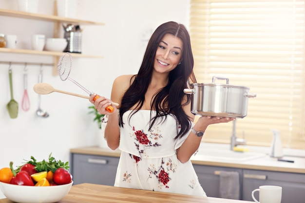Young woman trying to cook something in kitchen