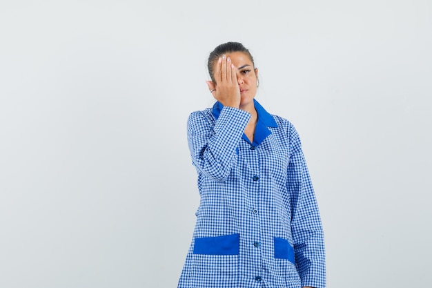 Young woman trying cover eye with hand in blue gingham pajama shirt and looking serious , front view.