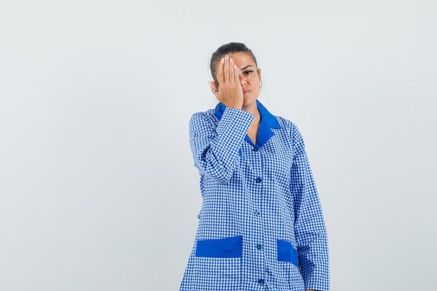 파란색 깅엄 파자마 셔츠에 손으로 커버 눈을 시도하고 심각한, 전면보기를 찾고 젊은 여자.