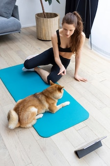 Young woman trying to exercise next to her dog