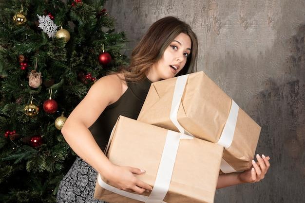 Giovane donna che cerca di tenere i regali di natale davanti alla cornice