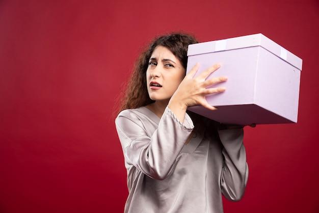 Giovane donna che prova ad ascoltare la confezione regalo viola.