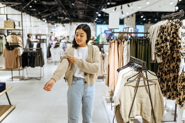 衣料品店でカーディガンを試着している若い女性