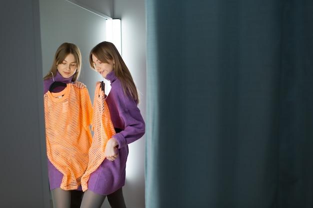 Молодая женщина примеряет одежду в магазине гардеробной