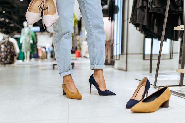 衣料品店で靴を履こうとしている若い女性、足で見る