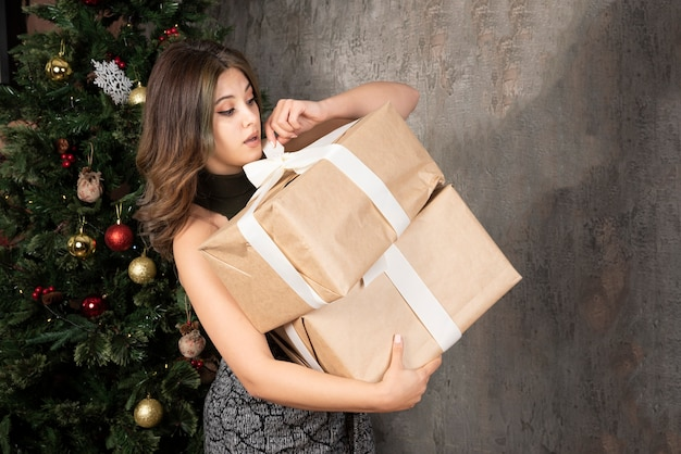Young woman trying to open christmas presents in front of pinetree