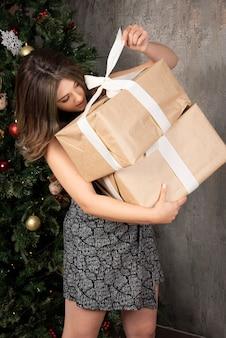 Giovane donna che cerca di aprire i regali di natale davanti al pino